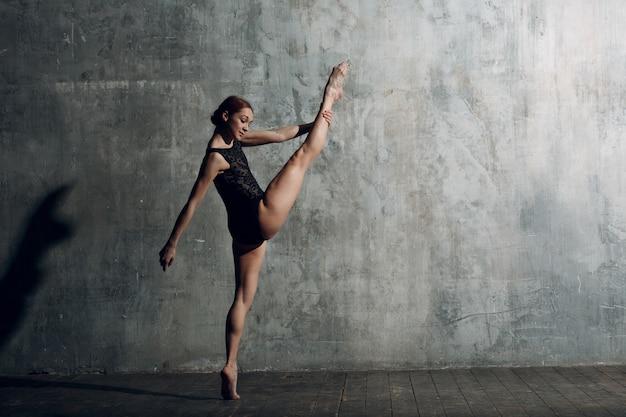 バレリーナストレッチ。プロの服、トウシューズ、黒体に身を包んだ若い美しい女性バレエダンサー。 Premium写真