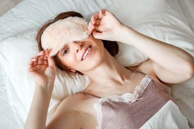 上から、おやすみの安静後に眠っているマスクを外して笑っている健康な若い女性の姿が撮影されています。 Premium写真