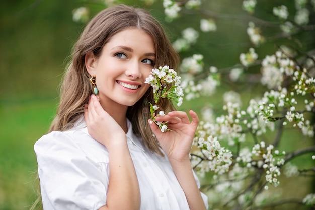 Красивая женщина с цветами весны цветущие на дереве. Premium Фотографии
