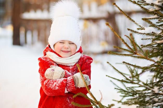 Маленькая девочка в красном пальто зимой, замерзла Premium Фотографии