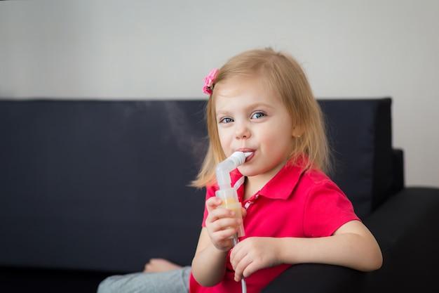 小さな女の子はネブライザーで気管支炎を扱います Premium写真