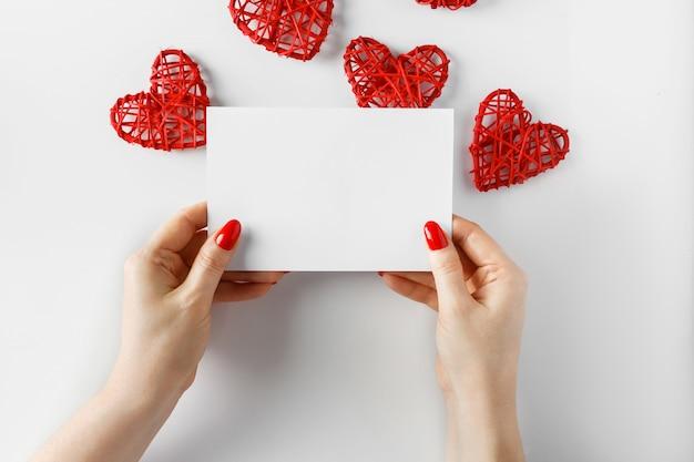 バレンタインデーのための白の手でグリーティングカード。 Premium写真