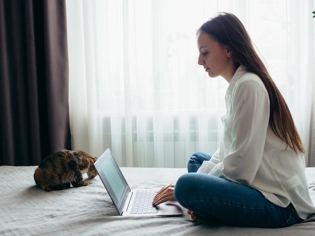 少女は、自宅で猫を座っている間、オンラインで学び、働き、自己啓発します。 Premium写真