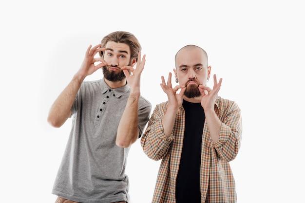 Двое мужчин гримасничают с усами, изолированное белое пространство, копией пространства Premium Фотографии