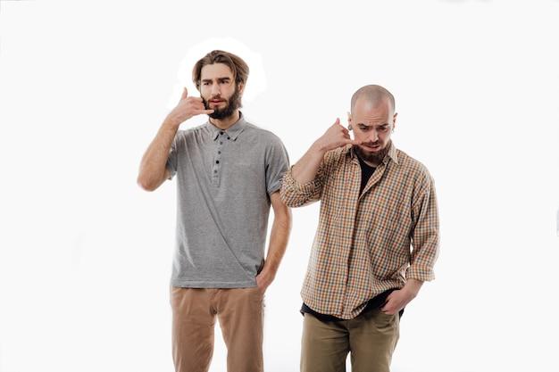 Двое мужчин подражают разговору по телефону, изолированное белое пространство, изолированное пространство, изолированное Premium Фотографии