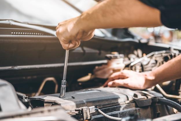ガレージで働く自動車整備士技術者自動車修理で働く自動車整備士の手 Premium写真