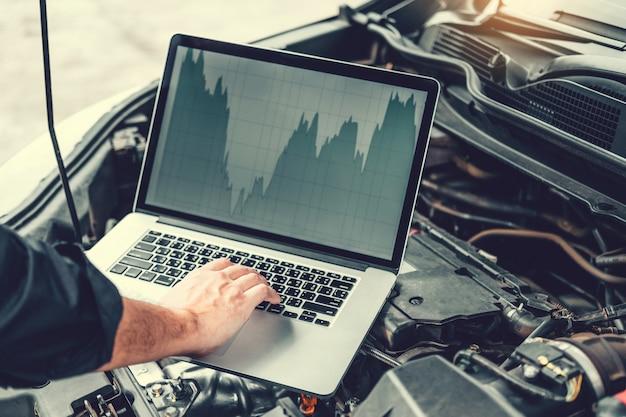 Профессиональный техник руки проверки службы ремонта двигателя автомобиля с помощью ноутбука на автомобиле Premium Фотографии