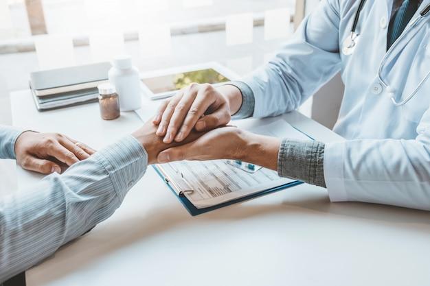 慰めと患者の病院と医学の概念を慰めるために手を繋いでいる医者 Premium写真