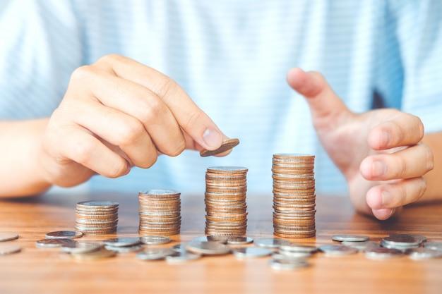 貯金コンセプトの男の手は予算のためのコインスタック財政を置く Premium写真