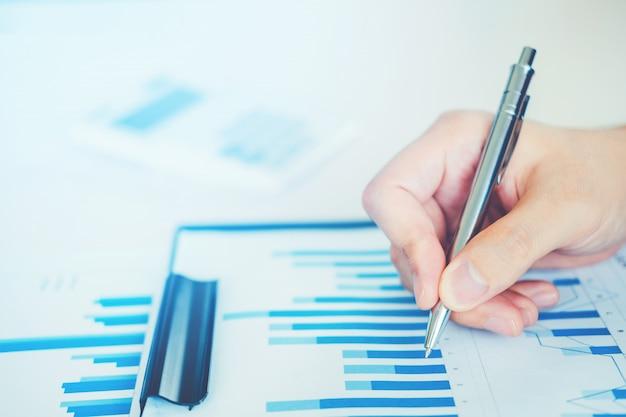 新しいビジネスプロジェクトを計画しているオフィスでレポートチャートを持つビジネスマン Premium写真