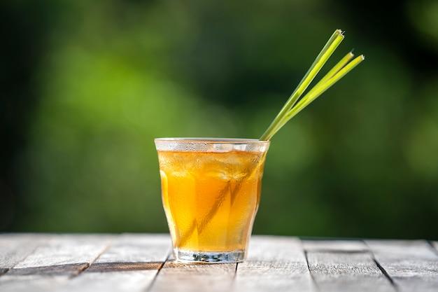トロピカルガーデンの木製テーブルにシナモンとレモングラスの茎の健康的でさわやかなドリンク Premium写真