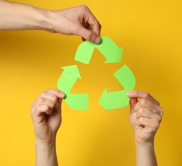 黄色の背景にリサイクルサインを保持している手、クローズアップ Premium写真