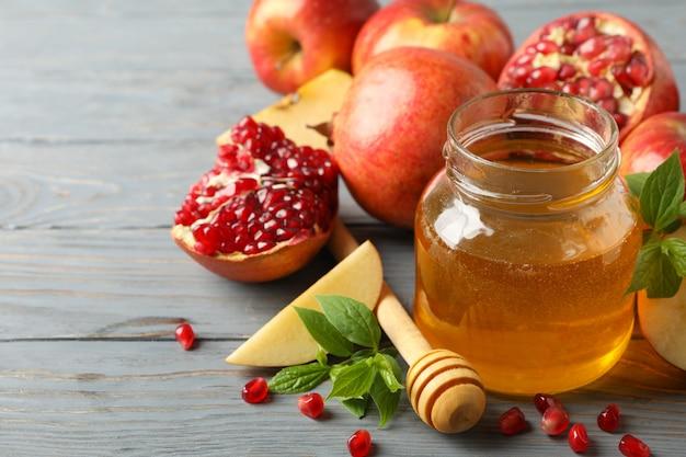 Яблоко, мед и гранат на дереве, крупным планом. домашнее лечение Premium Фотографии