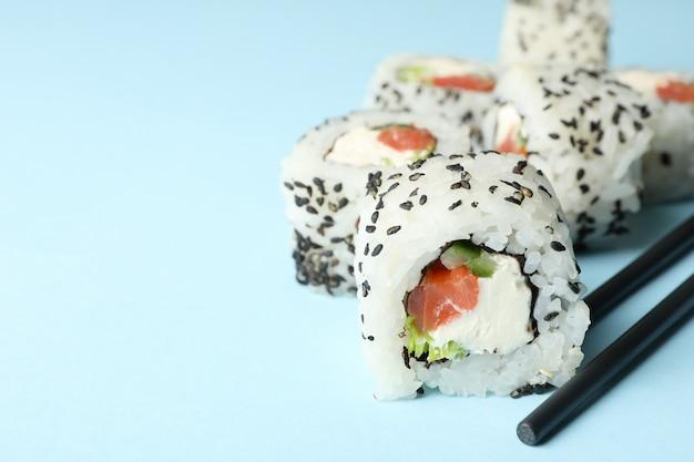 Палочки для еды и суши роллы на синей поверхности. японская еда Premium Фотографии