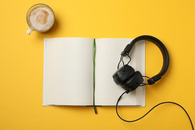 空白の本、ヘッドフォン、黄色のスペース、トップビューでコーヒーカップ Premium写真