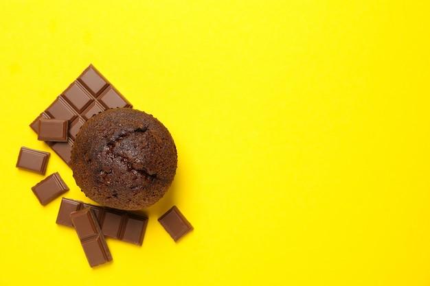 Вкусный кекс и шоколад на желтом фоне, вид сверху Premium Фотографии
