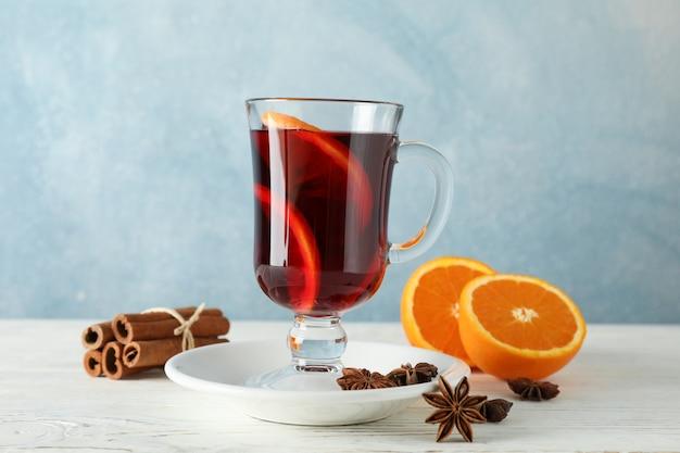 グリューワイン、オレンジ、シナモンの白い木製のテーブル Premium写真