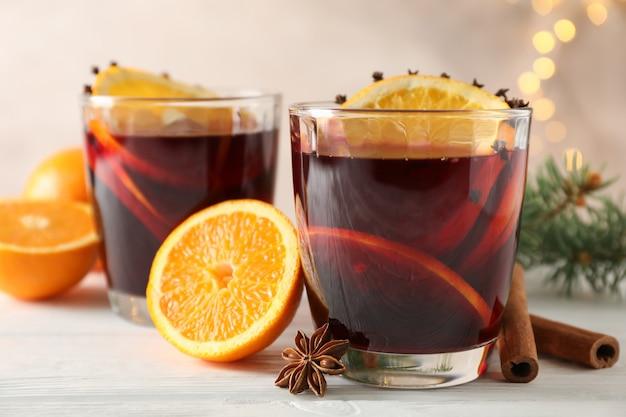白い木製のテーブルにオレンジとおいしいグリューワインのグラス Premium写真
