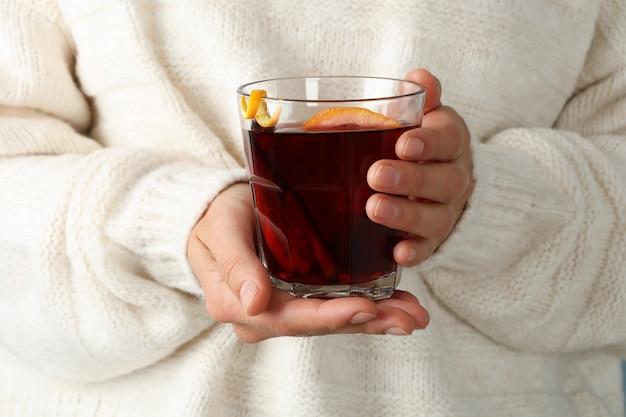 Девушка в свитере держит стакан с глинтвейном, крупным планом Premium Фотографии
