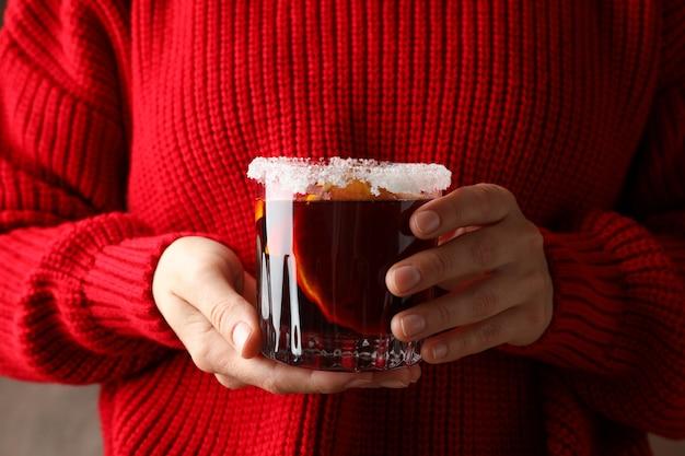 Девушка в красном свитере, держа бокал с глинтвейном, крупным планом Premium Фотографии