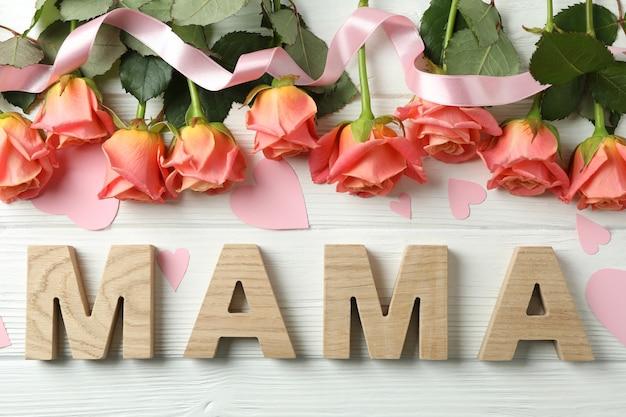 Надпись мама с розовыми розами, лентой и маленькими сердечками на деревянном столе, вид сверху Premium Фотографии