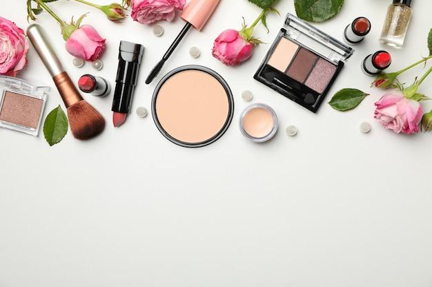Различная косметика для макияжа и цветы на белом фоне Premium Фотографии