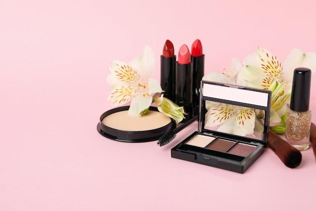 Разная косметика для макияжа и цветы на розовом фоне Premium Фотографии