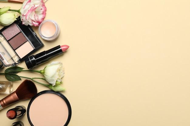 Разная косметика для макияжа и цветы на бежевом фоне Premium Фотографии