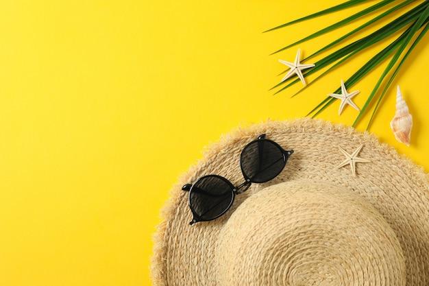麦わら帽子、サングラス、ヒトデ、ヤシの葉のテキストとトップビューの色背景スペース。夏休みのコンセプト Premium写真