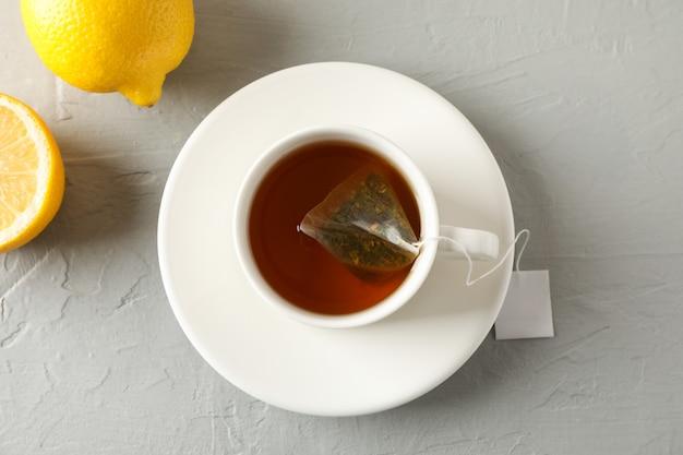Чашка чая с чайным пакетиком и лимонами на сером, вид сверху Premium Фотографии