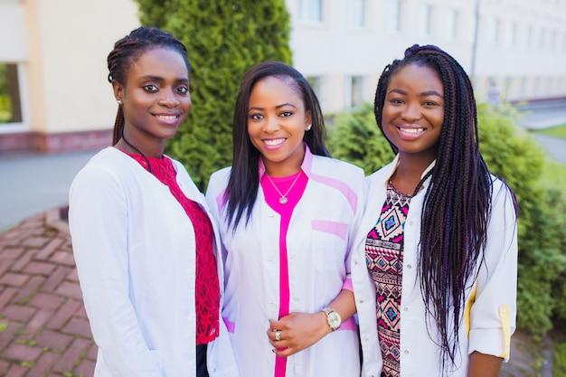 Счастливые выпускники медицинской бригады. портрет медицинского персонала в больнице. черные подружки врачи Premium Фотографии