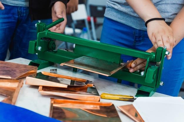 機械の屋根葺き職人が金属タイルを作る Premium写真