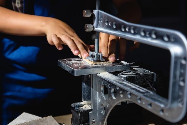 若い男が電動フレットソーで合板にパターンをカット Premium写真