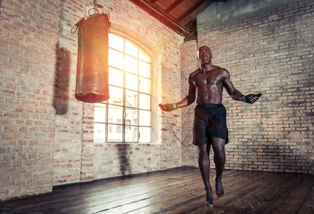 Черный боец усердно тренируется в своем спортзале Premium Фотографии