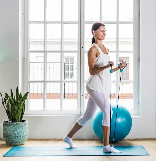 Красивая девушка делает тренировки и йоги дома утром Premium Фотографии