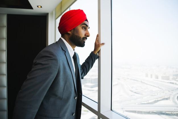 Индийский бизнесмен, глядя в окно в своем кабинете Premium Фотографии