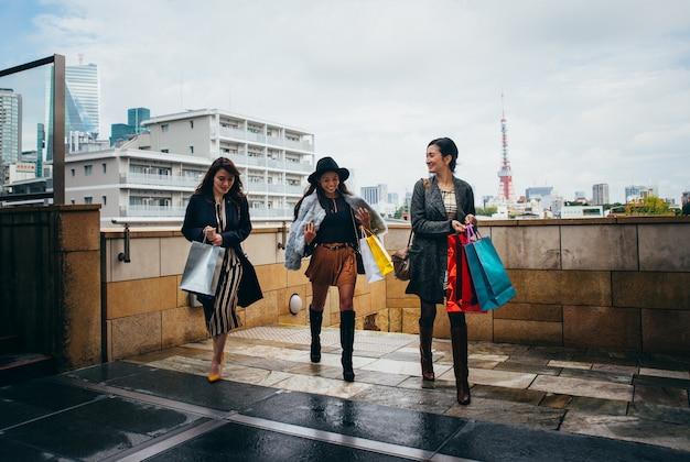 Группа японских женщин, проводящих время в токио, совершающих покупки в разных районах города Premium Фотографии