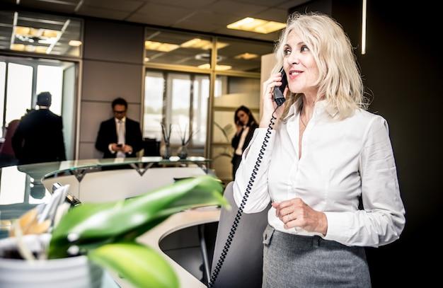 オフィスで電話に応答する秘書 Premium写真