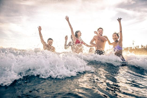 ビーチで大きなパーティーやゲームを作る友人のグループ Premium写真
