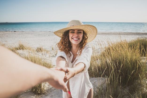 若いカップルがビーチで幸せと愛の気分を共有 Premium写真