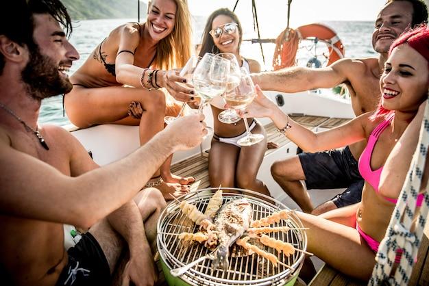ヨットで魚のバーベキューを作る友人 Premium写真