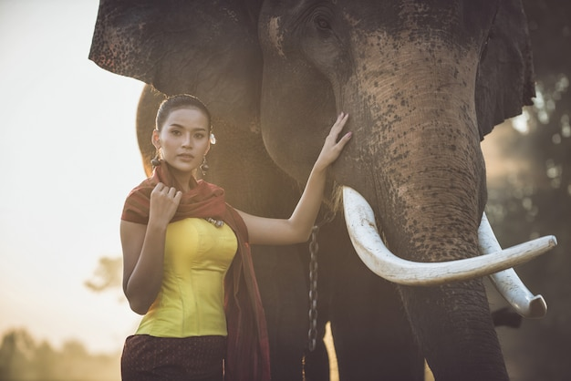 Красивая тайская женщина проводит время со слоном в джунглях Premium Фотографии