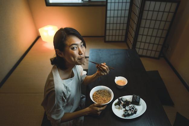 Японка ест в традиционной квартире Premium Фотографии