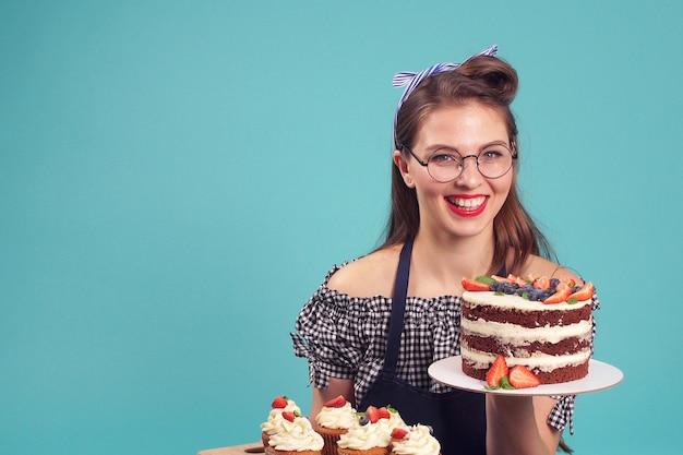 Счастливый кондитер позирует для камеры с тортом в руках Premium Фотографии