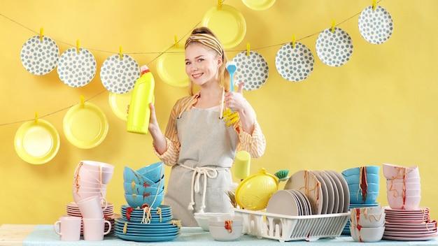 美しい女性は、汚れた皿を洗うための効果的な液体を宣伝しています。広告のコンセプト Premium写真