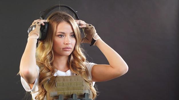 Довольно молодая женщина с длинными волосами, одетые в военную форму, позы, изолированные на темной стене с дымом на заднем плане. Premium Фотографии