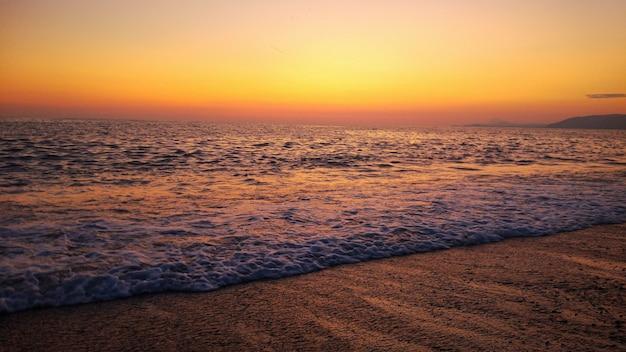 Сочетание заката и пляжа. красочный оранжевый закат на пляже Premium Фотографии