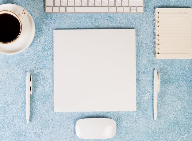 Офисный стол с рабочими принадлежностями, мышью, клавиатурой, кофейной чашкой и блокнотом. вид сверху, флэтли. Premium Фотографии