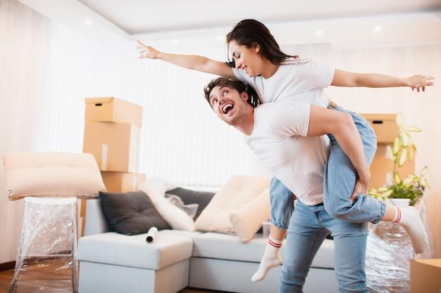 幸せな夫と妻は、一緒に自分のアパートに引っ越すことを楽しんでいます。引っ越しの日に段ボール箱の近くのリビングルームで大喜びの若いカップルのダンスを楽しませる、 Premium写真