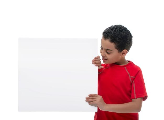 Молодой улыбающийся мальчик держит доску с копией пространства Premium Фотографии
